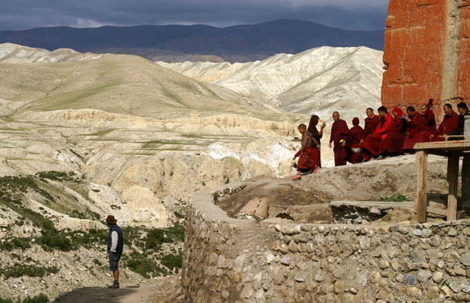 Lo Manthang, Upper Mustang, Nepal: An ATS traveller absorbs the scene and relaxed monks catch some late afternoon sun – looking across to Tibet where, unlike Mustang, the Buddhist monasteries have suffered decades of repression.